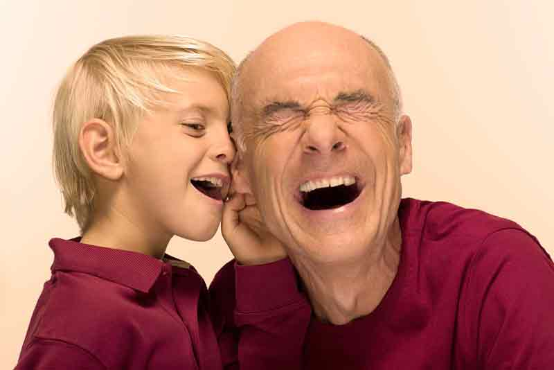 boy whispering in mans ear with Widex hearing aid