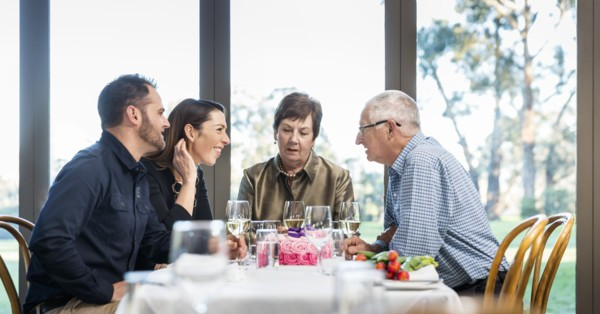 family having a meal together discussing hearing loss