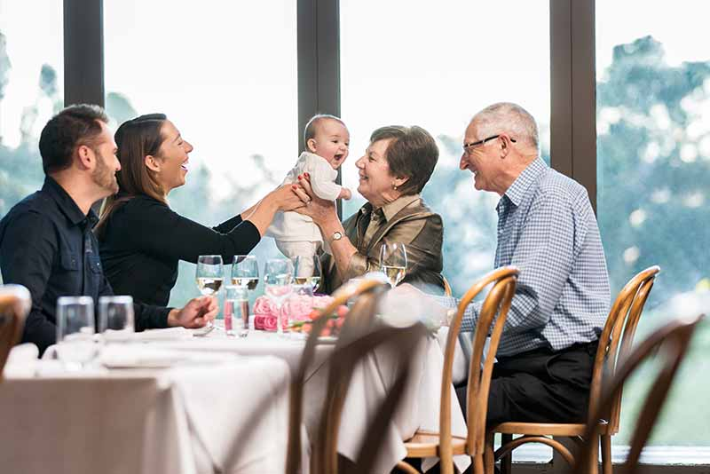 Parents and grandparents with kid having lunch